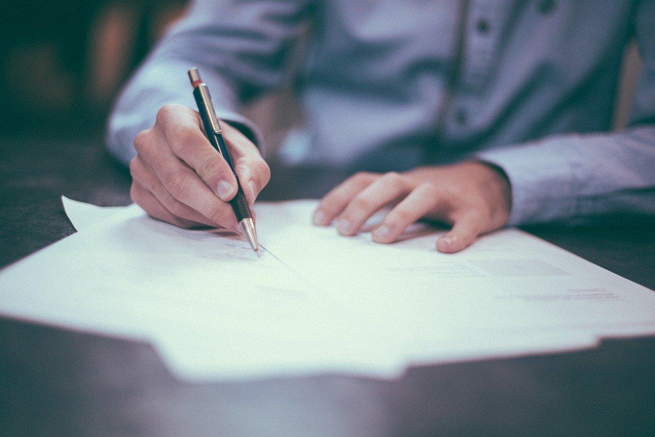 Человек подписывает документы.